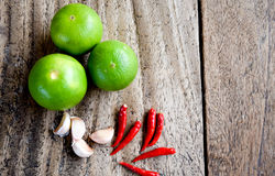 Chili, garlic and lime on wooden table, Asian herb and spicy royalty free stock photography