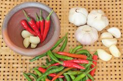 Chili and garlic in mortar on wooden textured Stock Photos