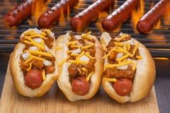 Chili Hot Dogs Grilled i bullar och på grillfestgaller Arkivbilder