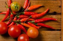 Chili i pomidor na drewnianym tle Obrazy Stock