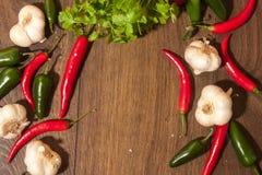 Chili, jalapeno, garlic and coriander background. On wooden ground Stock Photo