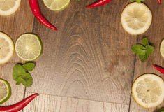 Chili, lime, mint and lemon background. On wooden background Stock Images