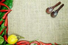 Chili med det ljust rödbrun kaffirlimefruktbladet med den thai löken på säckvävbakgrund Royaltyfria Bilder
