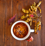 Chili. With melted cheese on top, on an aged wooden table, surrounded by fall leaves Royalty Free Stock Photography