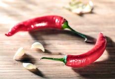 Chili och vitlök på en tabell Arkivfoto