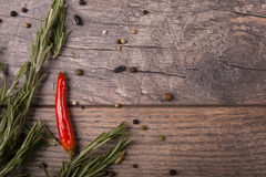 Chili paprika and green rosemary on a wooden background. Mexican restaurant concept. Black and red pepper. Copy space. Royalty Free Stock Images