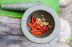 Chili paste in mortar. Grill chilli garlic onion and pound in mortar stone Stock Image