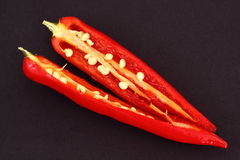 Chili pepper. A red chilli pepper on a black background Stock Photos