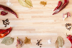 Chili pepper, bay leaf, black pepper, garlic, salt. Spices on light wooden background with copyspace Royalty Free Stock Image