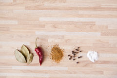 Chili pepper, bay leaf, black pepper, salt. Spices on light wooden background with copyspace Stock Photos