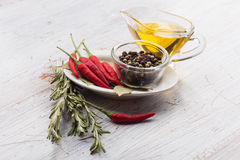 Chili pepper, black peppers, rosemary, oil, bay leaves Royalty Free Stock Photo