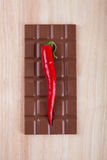 Chili pepper and chocolate on chopping board Stock Photos