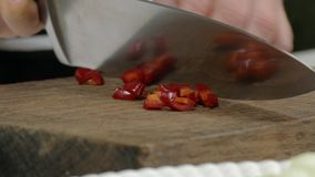 Chili pepper chopping with knife stock video footage