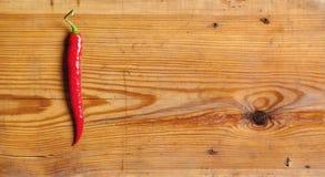 Chili pepper on a decorative board. One chili peppers on a decorative board Royalty Free Stock Photos