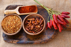 Chili pepper, fresh, dried, crushed and as powder. Chili pepper, fresh pods on a bunch, dried in wooden bowl, crushed in a wooden bowl and as powder on wooden Royalty Free Stock Image