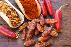 Chili pepper, fresh, dried, crushed and as powder. Fresh chili pods, dried, crushed and as powder on wooden scoops on a rustic wooden table Stock Photography