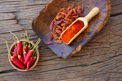 Chili Pepper, fresh, dried and Powdered. Red Chili Pepper, fresh pods, dried and Powdered in a wooden bowl and on an old spice scoop on a rustic wooden table Stock Image