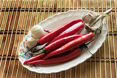 Chili pepper and garlic. On a table in a plateau chili pepper lies Royalty Free Stock Image