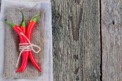 Chili pepper on linen texture and wooden table,spice Stock Images