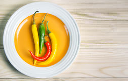 Chili pepper on plate on wooden background. Stock Photography