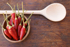 Chili pepper pods in a bowl. Red Chili pepper pods in a bowl and wooden cooking spoon on an old rustic wooden table with copy space Royalty Free Stock Image