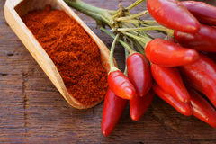 Chili pepper pods and chili powder. Chili pepper pods as bunch and chili powder on a wooden spice scoop on a rustic wooden table Stock Photo