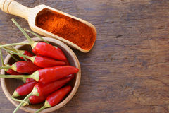Chili pepper pods and chili powder. Fresh chili pods in a wooden bowl and chili powder on a wooden spice scoop on a rustic wooden table with copy space Royalty Free Stock Image