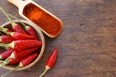 Chili pepper pods and chili powder. Fresh chili pods in a wooden bowl and chili powder on a wooden spice scoop on a rustic wooden table with copy space Royalty Free Stock Photography