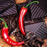 Chili Pepper rouge avec la barre de chocolat coupée sur le fond en bois Photos stock