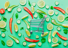 Chili pepper and shopping cart with lemons Stock Images