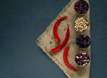 Chili pepper, spices and beans on a blue concrete background, concept of healthy vegetarian food. Top view, free text space stock photos