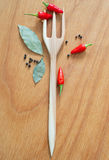 Chili pepper still life with wooden fork. Still life of bunch of chili pepper, black pepper, nutmegs, peppercorn and bay leaves with wooden fork trident on the Royalty Free Stock Photos