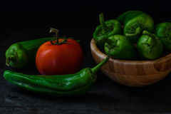 Chili pepper and tomato on dark background. Chili pepper and tomato on a dark background. some pepper lie in a wooden bowl. the ingredients for the sauce stock photography