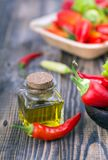 Chili pepper with pepper oil. Chili pepper in wooden bowl with pepper oil in small bottle royalty free stock photo