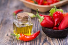 Chili pepper with pepper oil. Chili pepper in wooden bowl with pepper oil in small bottle stock photo