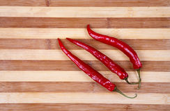 Chili peppers. 3 red hot chili peppers on breadboard Stock Photos