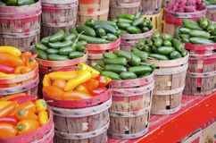 Chili Peppers. Baskets of fresh hot orange and red chili peppers and green jalapeno peppers for sale the outdoor market Stock Photo