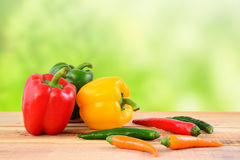 Chili peppers and bell peppers on wooden. Royalty Free Stock Photos