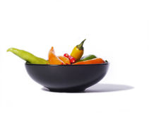 Chili peppers in a black bowl, isolated on white Stock Photo