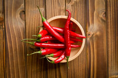 Chili peppers in bowl on wooden table Royalty Free Stock Photo
