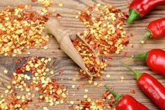 Chili Peppers caliente, las pimientas molidas forma escamas en el tablero de madera Imagen de archivo