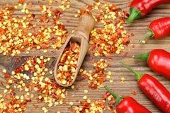Chili Peppers caliente, las pimientas molidas forma escamas en el tablero de madera Imagenes de archivo