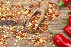 Chili Peppers caliente, las pimientas molidas forma escamas en el tablero de madera Fotos de archivo