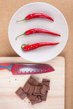 Chili peppers with chocolate and knife Royalty Free Stock Image