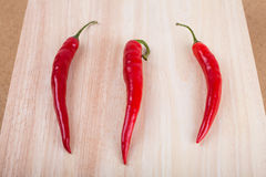 Chili peppers on chopping board Stock Images
