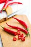 Chili peppers on cutting board Stock Photo