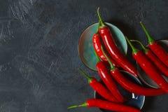 Chili Peppers d'un rouge ardent dans des cuvettes sur le vieux fond Photos stock