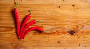 Chili peppers on a decorative board. Four chili peppers on a decorative board Royalty Free Stock Photo