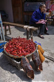 Chili peppers drying next to shoe, in Chinese minority village. Stock Photos