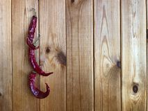 Chili peppers on a wood background. Chili peppers drying on the wall. Chili peppers on a wooden background. dried chili pepper. Dry chili stock image